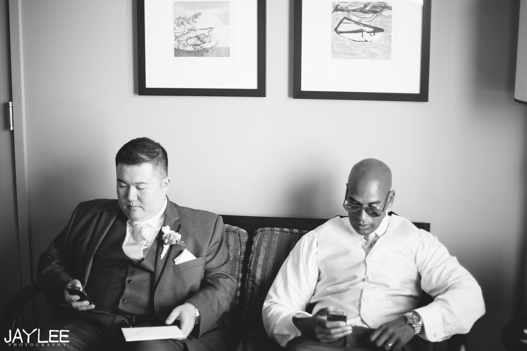 groom and best man checking phones in hotel room seattle, washington