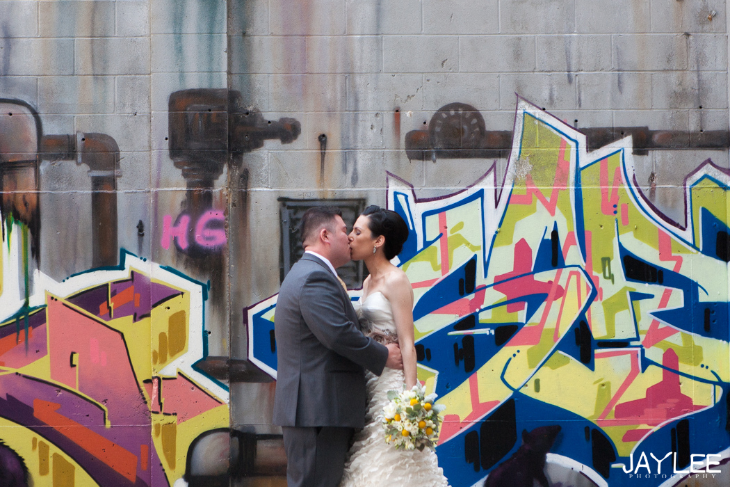 bride and groom kissing in front of graffiti in downtown seattle