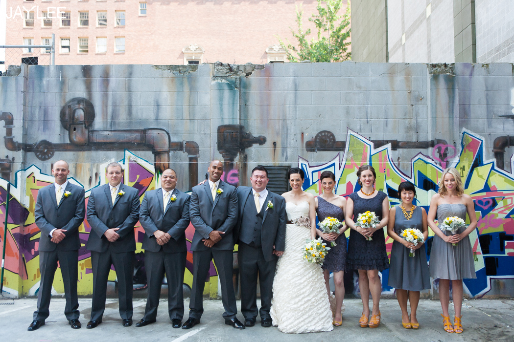 yellow and grey wedding party in front of graffiti wall in downtown seattle