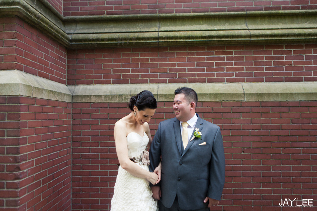 bride and groom laughing in front of brick wall at blessed sacrament church in seattle, washington