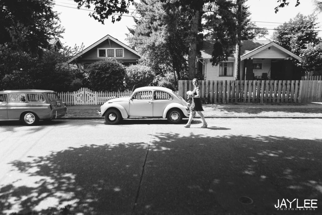 bridesmaid walking past vw beetle in university district seattle, washington