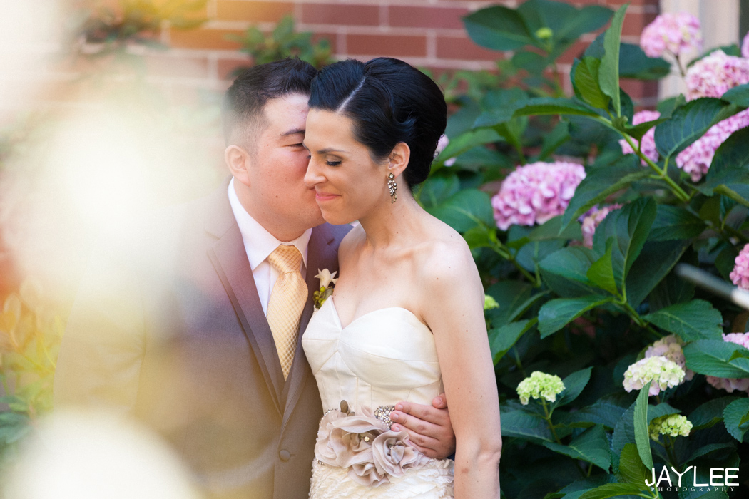 groom whispering to bride in front of bright flowers