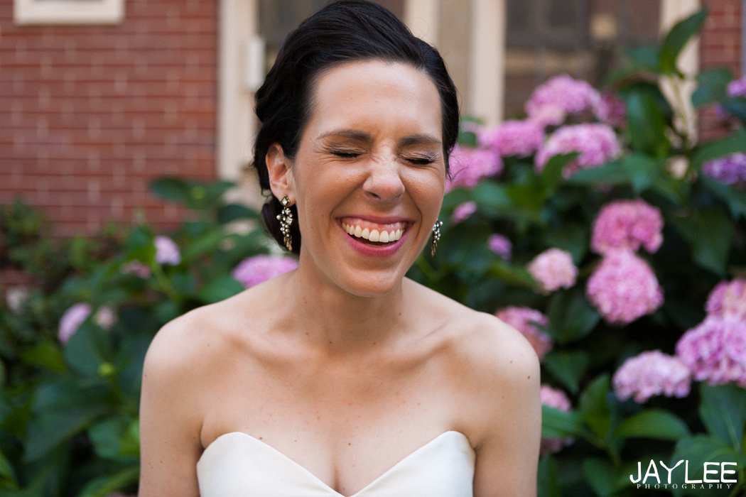 laughing bride in front of flowers at blessed sacrament in seattle, washington