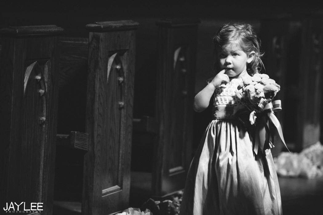flower girl walking down aisle of blessed sacrament in seattle