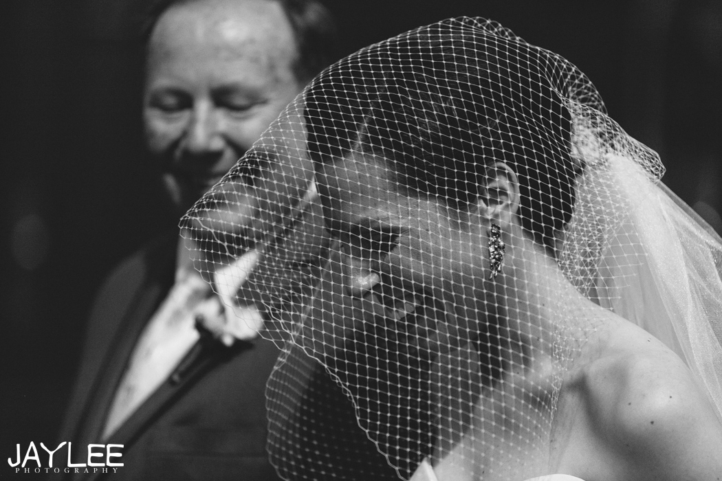 bride in mesh veil walking down aisle with her father