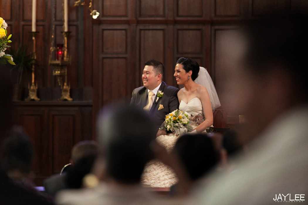bride and groom sitting during catholic ceremony at blessed sacrament in seattle, washington