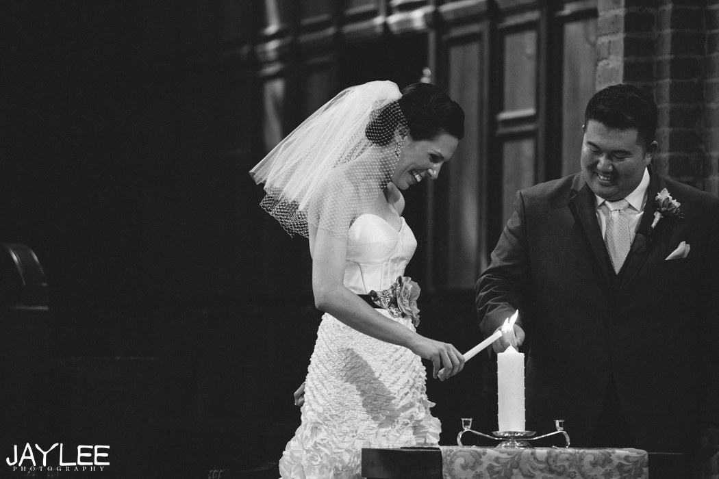 bride and groom light unity candle during wedding ceremony