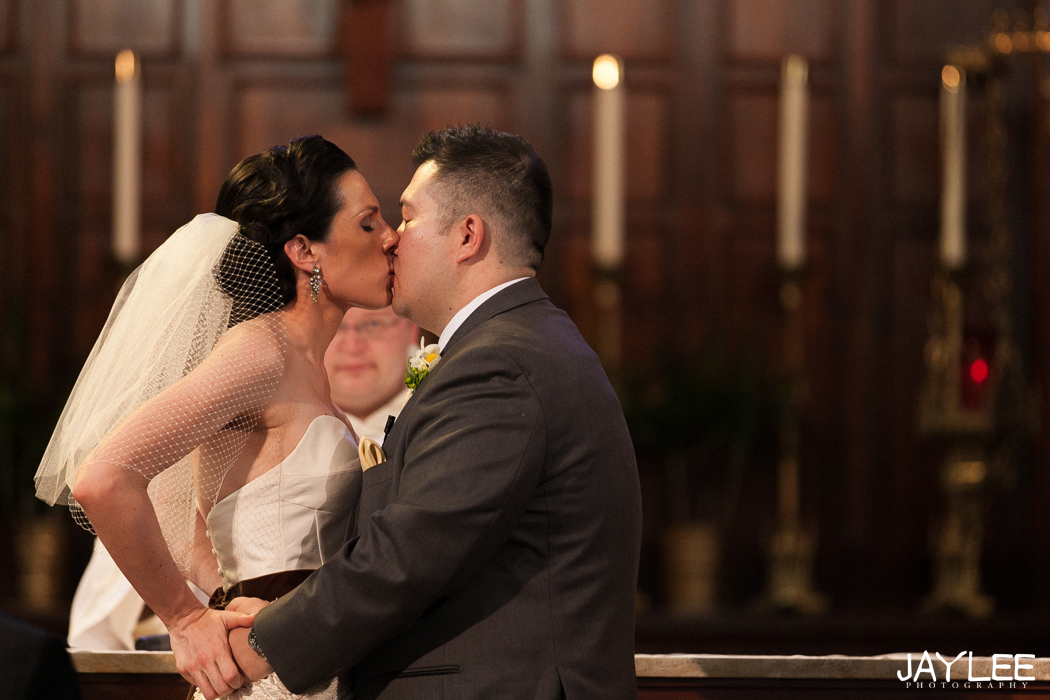 bride and groom share first kiss at blessed sacrament in seattle, washington