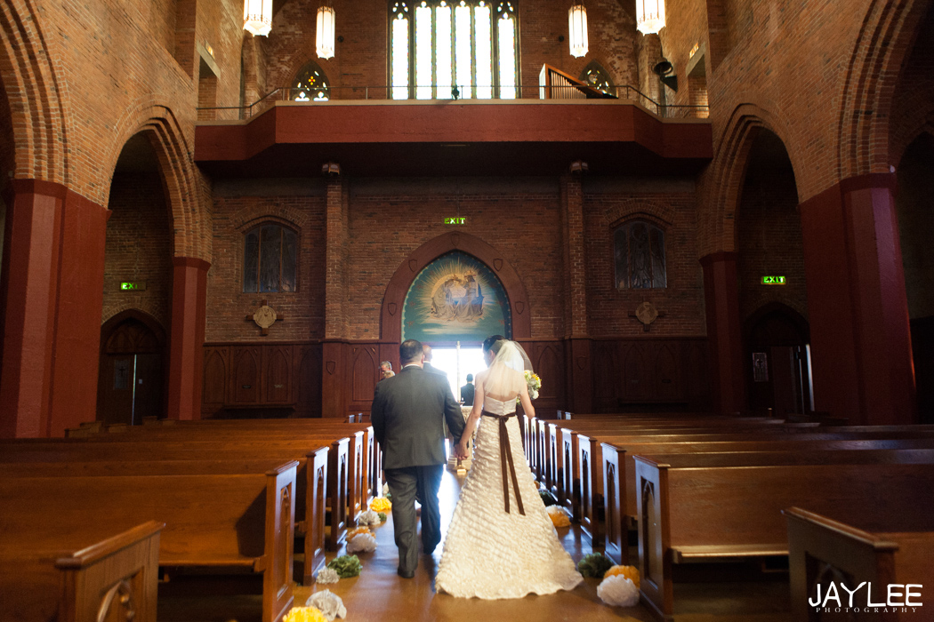 bride and groom walking down the aisle at blessed sacrament in seattle, washington