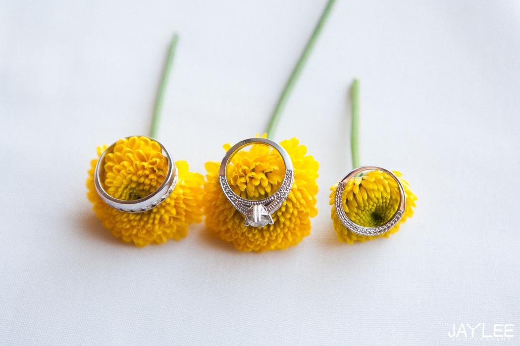 close up of wedding rings on yellow flowers