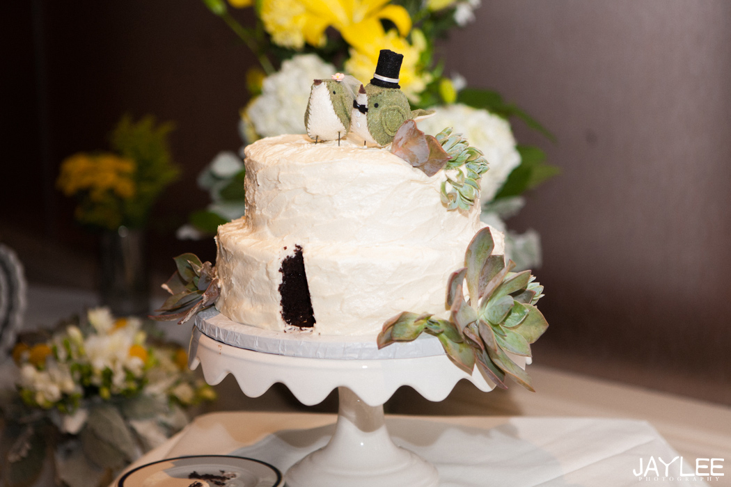 white wedding cake with cute vintage bird topper