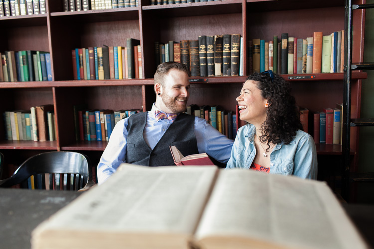 trendy couple laughing in library during engagement photos