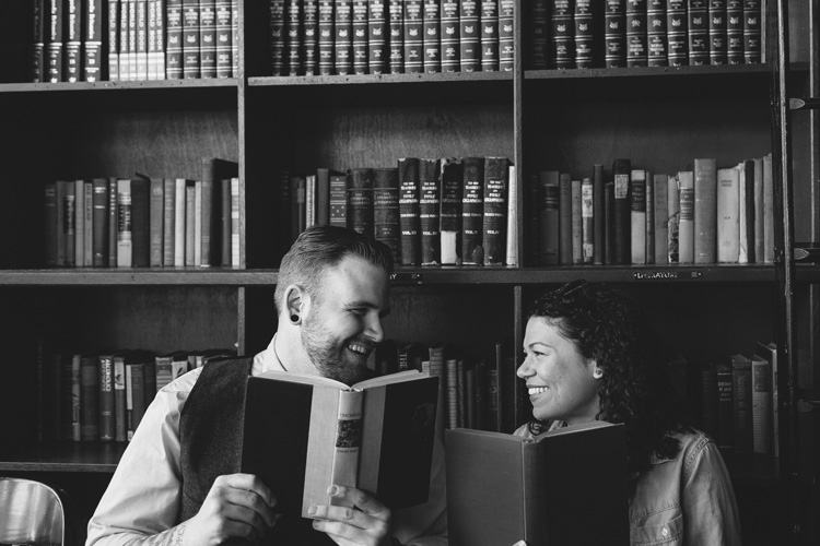 laughing couple behind books at coffee shop in seattle, wa