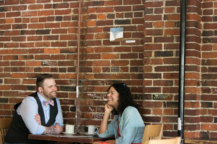 laughing engaged couple drinking coffee in seattle washington