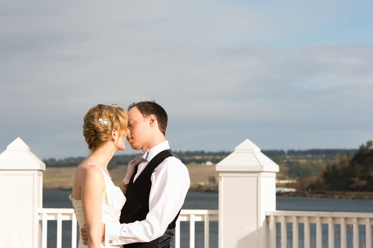 bride and groom kissing over water view