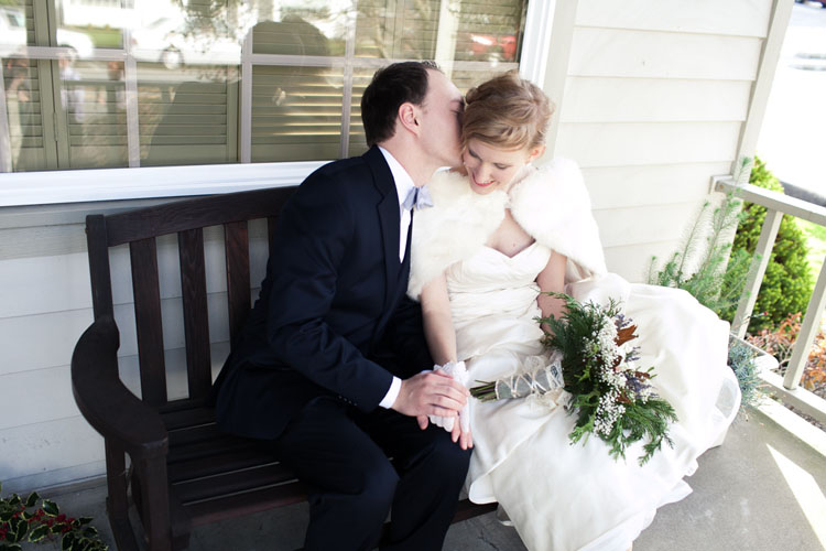 groom whispering to bride wearing white shrug