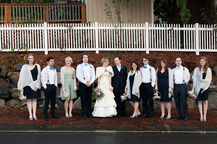 bridal party with grey suspenders, blue bow ties, black dresses and white shawls