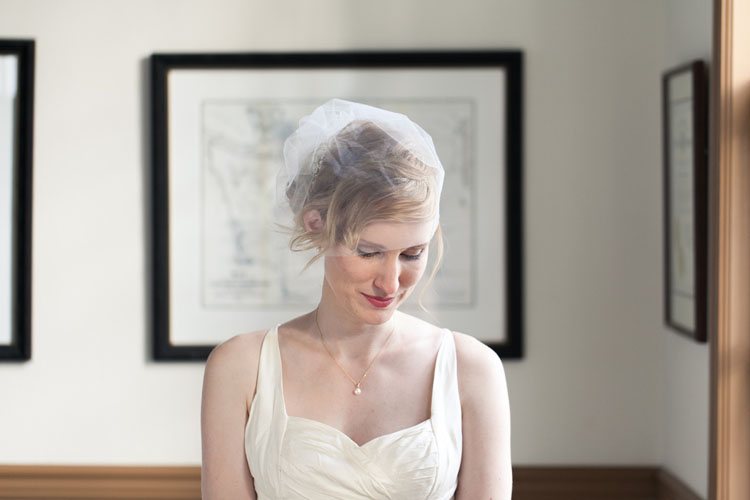 white Tulle birdcage wedding veil and white dress