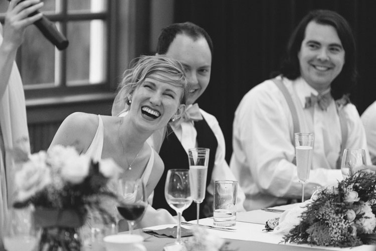 bride laughing at maid of honor toast