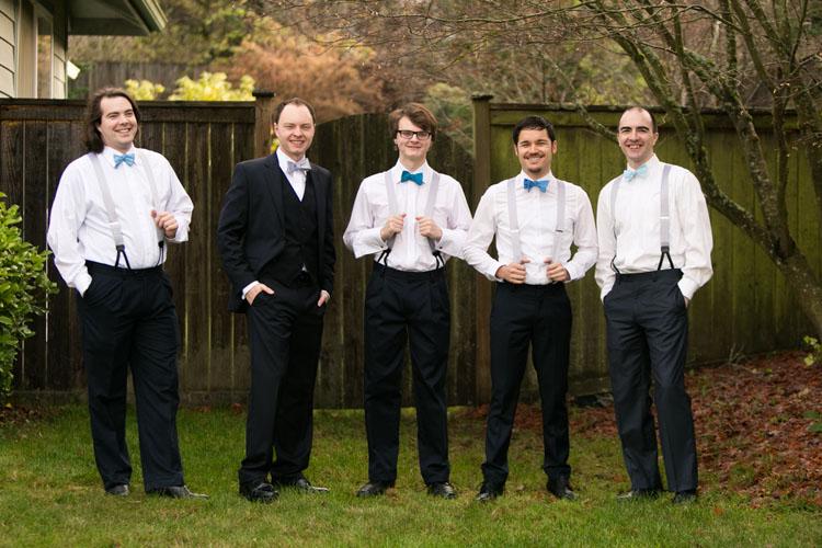 laughing groom and groomsmen in suspenders and bow ties