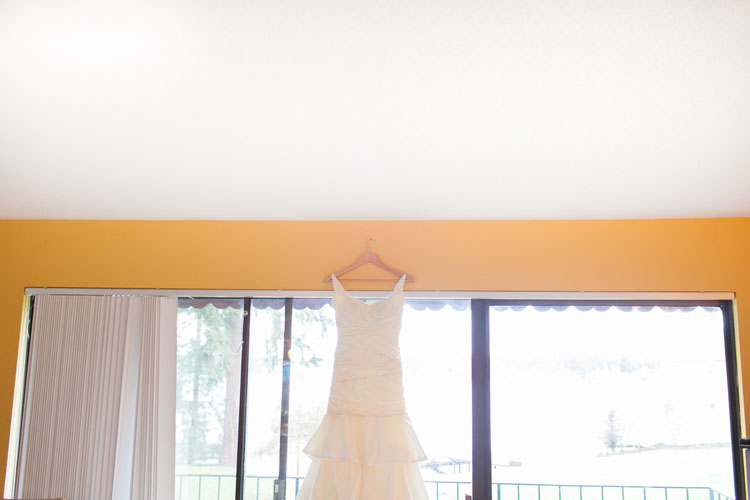 ivory wedding gown hanging in window of thornewood castle