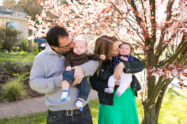 twins and family standing by a cherry blossom tree
