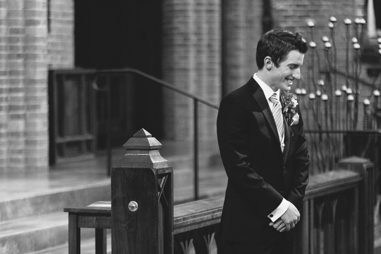 happy groom at altar