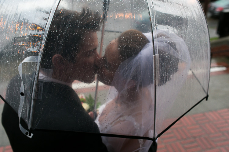 bride and groom kissing under umbrella in the rain