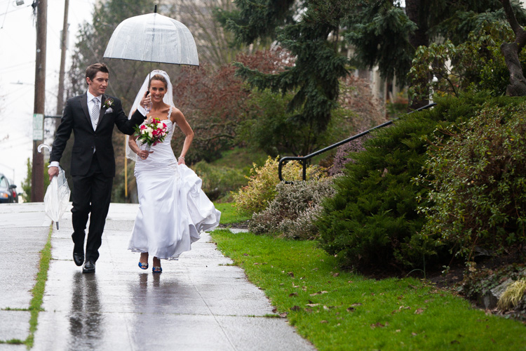 bride and groom walking under umbrella in the rain