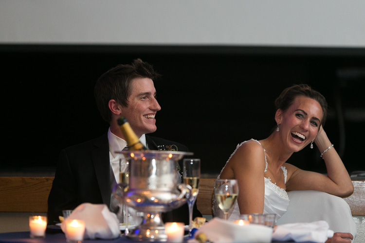 bride and groom laughing at toasts