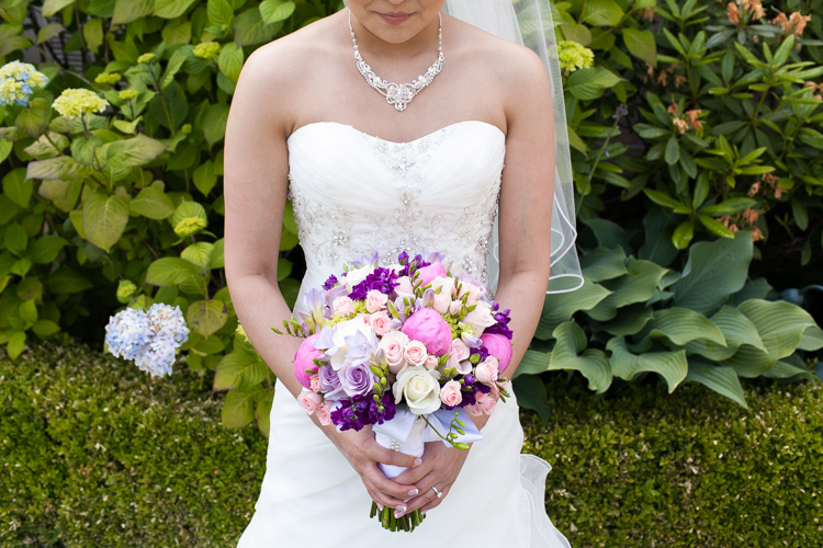 bride holding purple bouquet