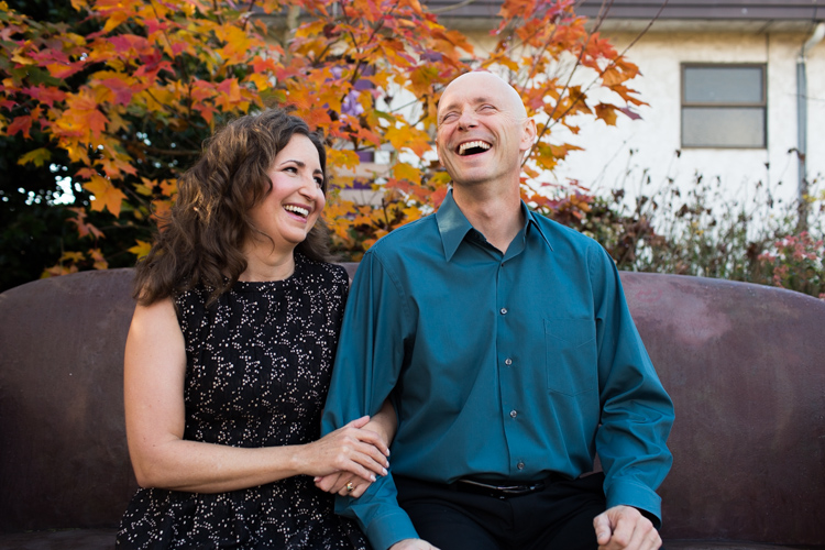 portrait session of couple laughing in Fall leaves at ballard corners park