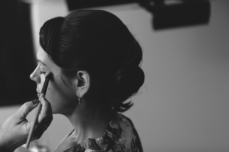 bride with hair up having makeup done