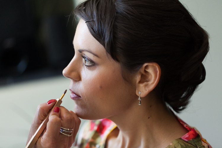 applying bridal lipstick on wedding day