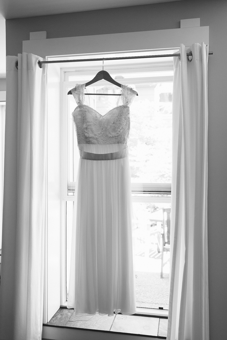 vintage wedding dress hanging in window