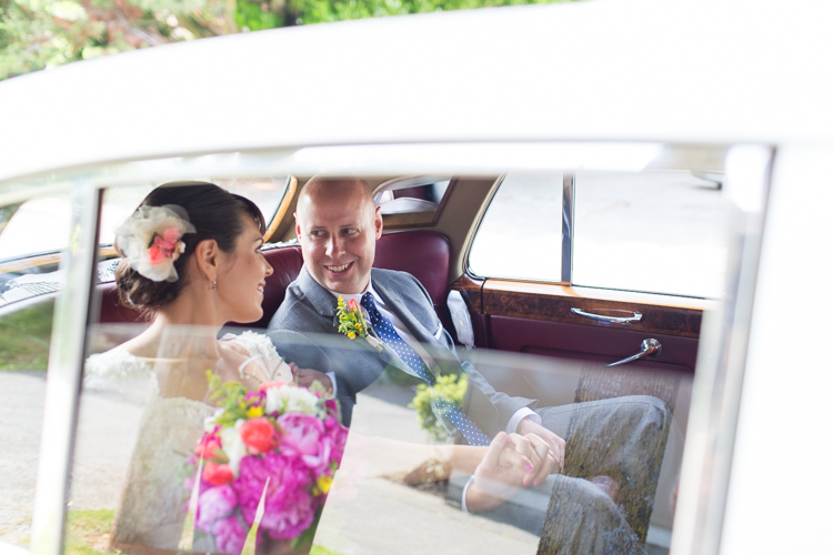 groom smiles at bride in british motor car