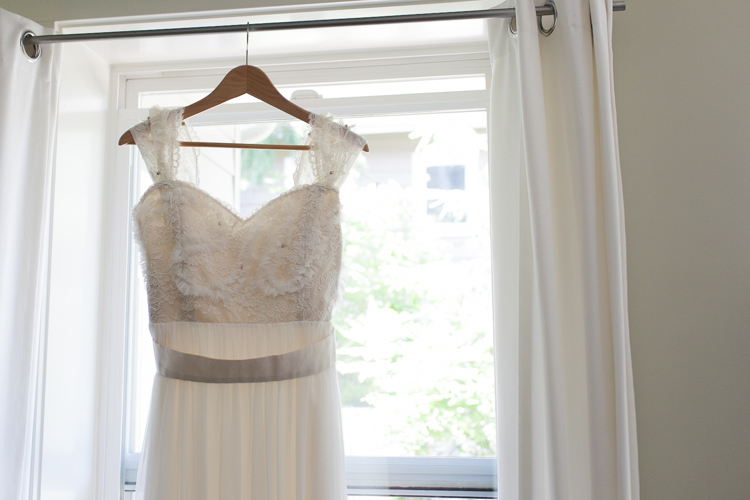 vintage style wedding dress hanging in window