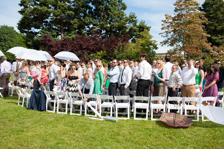 guests at outdoor wedding in the summer with umbrellas