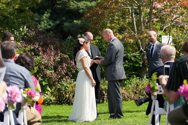 bride and groom exchange rings during sunny seattle wedding
