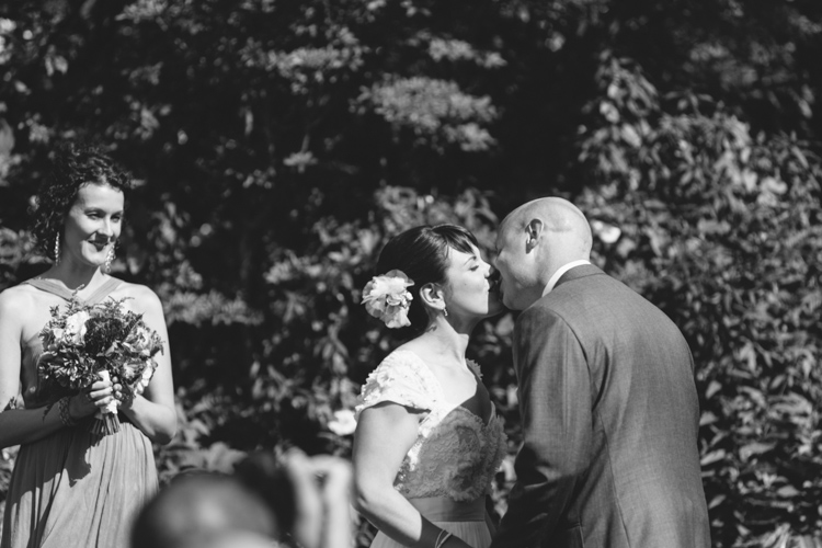 first kiss in sunny outdoor wedding ceremony