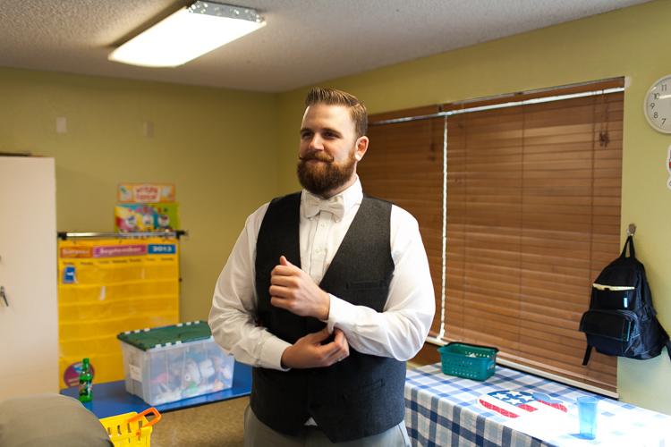groom in vest and green bowtie