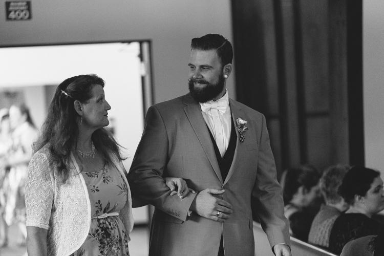 groom walking mother down aisle