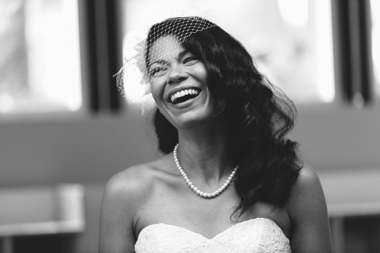 smiling bride with pearl necklace and birdcage veil