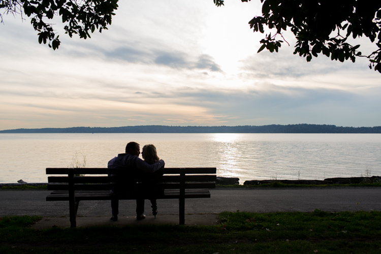 couple sitting on bench on beach at sunset