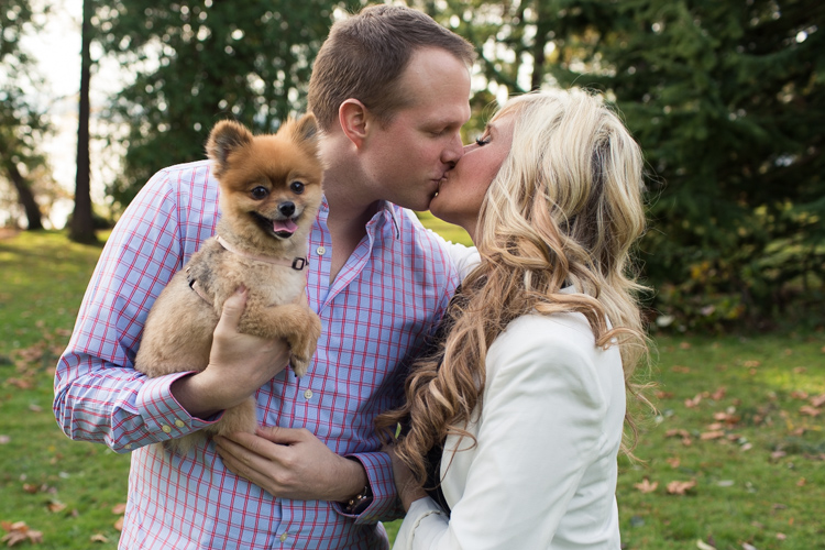 kissing couple holding dog