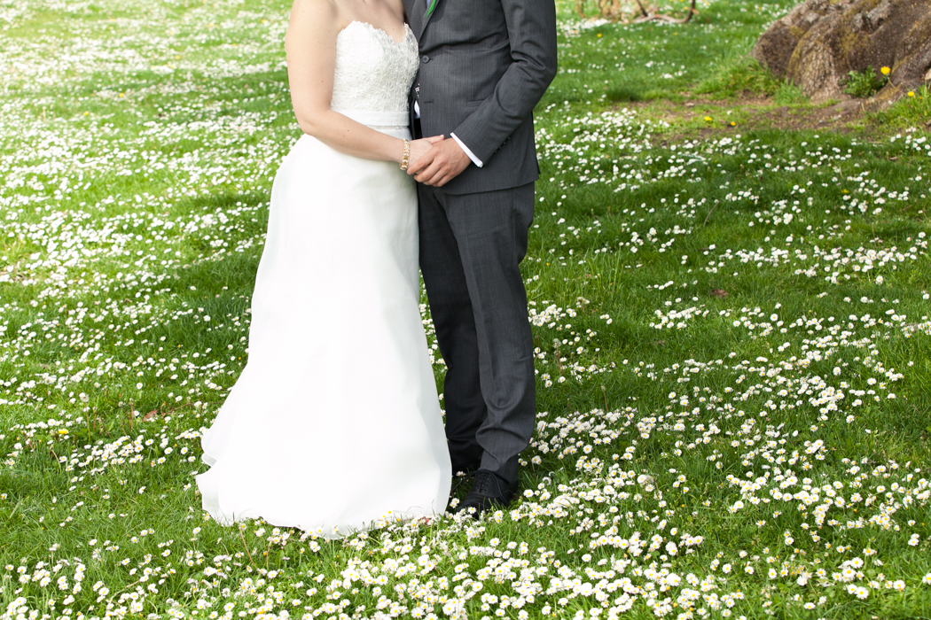 bride and groom in a field of white flowers