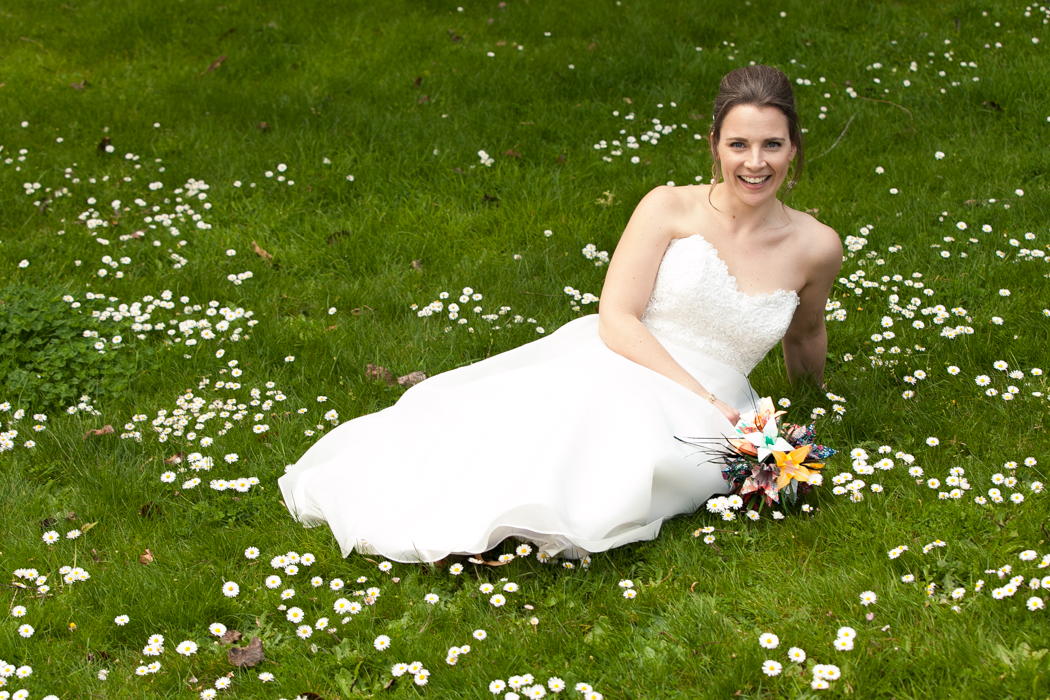 bride laying in a field of flowers