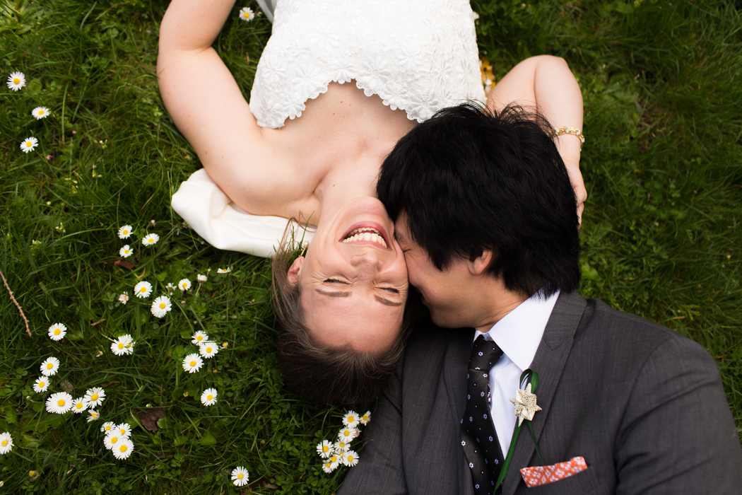 bride and groom laying in the grass
