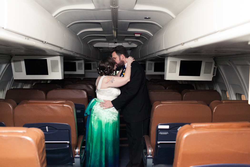 couples portrait in a plane. flight themed wedding