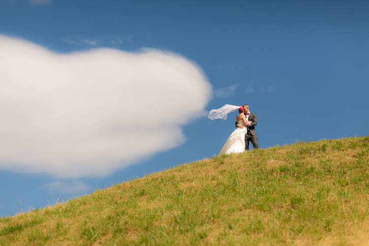 bride and groom on a hill veil blowing in the wind